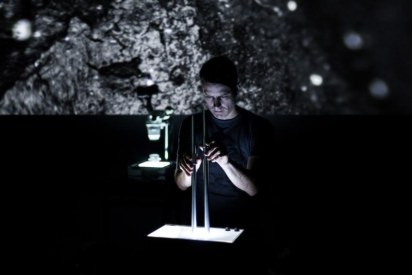Martin Messier manipule microscope, caméra et table lumineuse devant un écran qui retranscrit l'action.